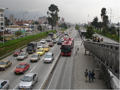 "Bogotá: Double lanes at stops permit express buses to pass at stations while ""bendy"" articulated buses allow greater passenger capacity per bus. Passengers access stations via walkways which bridge highways."