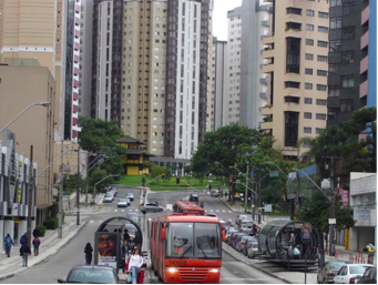 Curitiba: High-rise towers flank iconic tubular bus stations. Note the modern buses.