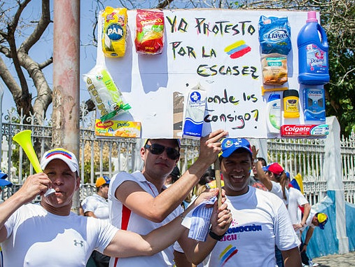 """Protestors highlight economic woes. The sign reads, """"I protest for the shortages: Where do I find these?"""""""