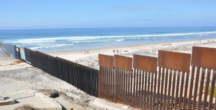 Fence at the U.S.-Mexico border extending into the Pacific Ocean